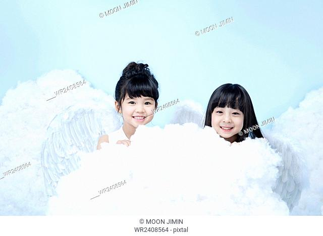 Two girls in angel costume behind clouds in the background representing heaven