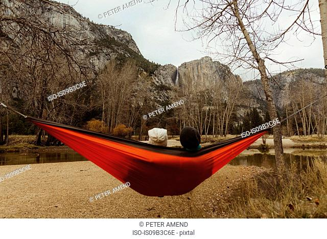 Rear view of couple reclining in red hammock looking out at landscape, Yosemite National Park, California, USA