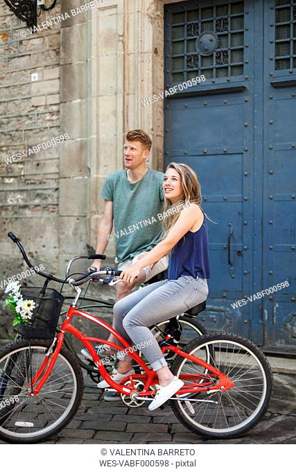 Couple with bicycles in front of an old church