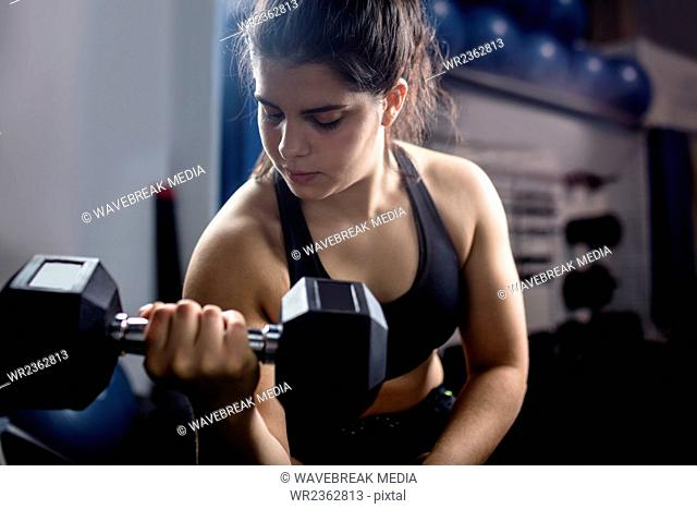 Woman exercise with dumbbells and working on her biceps