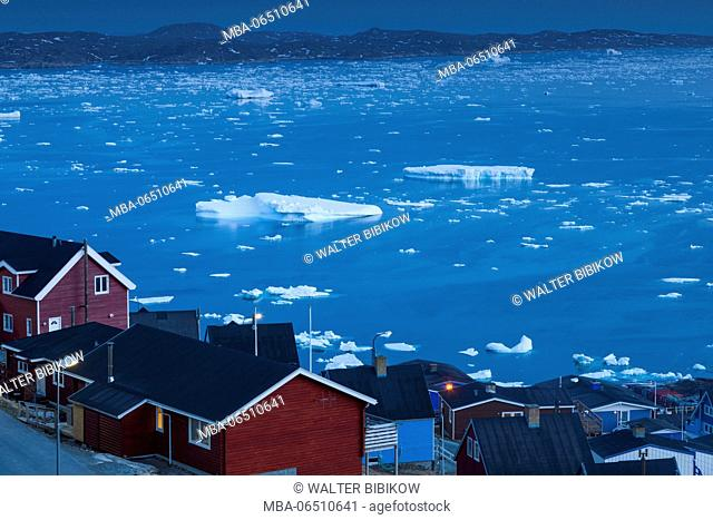 Greenland, Qaqortoq, elevated town view with floating ice, dusk