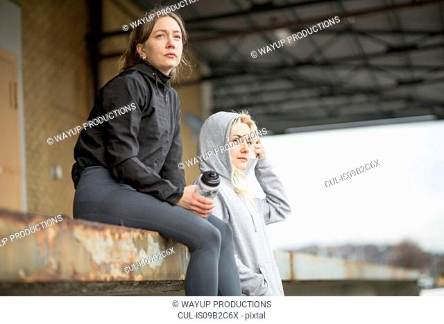 Two female runner friends looking out from warehouse platform