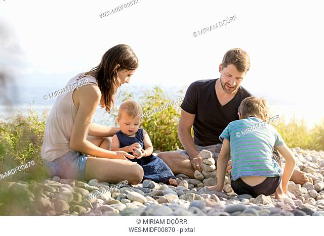 Germany, Friedrichshafen, Lake Constance, family playing with stones at lakeshore