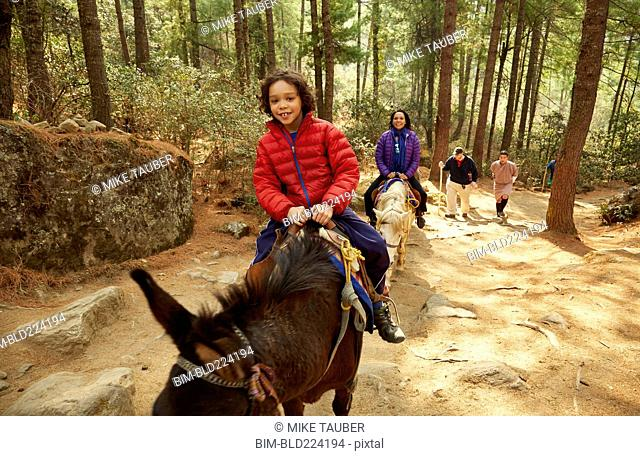 Mixed Race mother and son riding horses