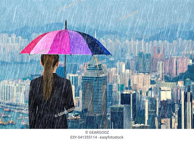 business woman holding multicolored umbrella with falling rain at city background