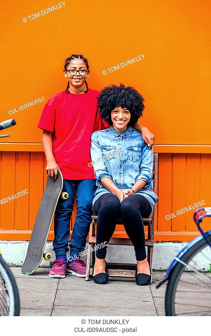 Portrait of boy and mother in front of orange wall