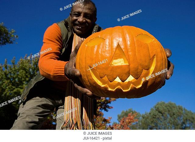 Senior man holding jack-o-lantern