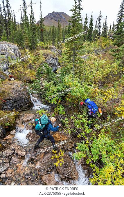 Backpackers cross a stream drainage along the Arrigetch Creek, Arrigetch Peaks, Gates of the Arctic National park, Alaska