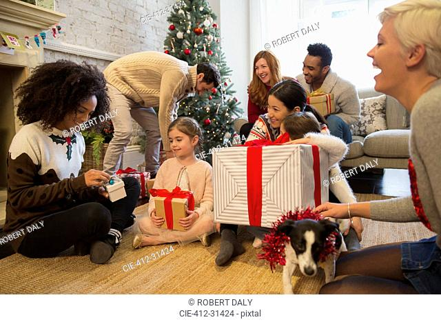Friends and family opening Christmas gifts in living room