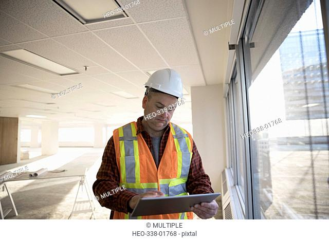 Contractor using digital tablet at window in empty, unfinished highrise office