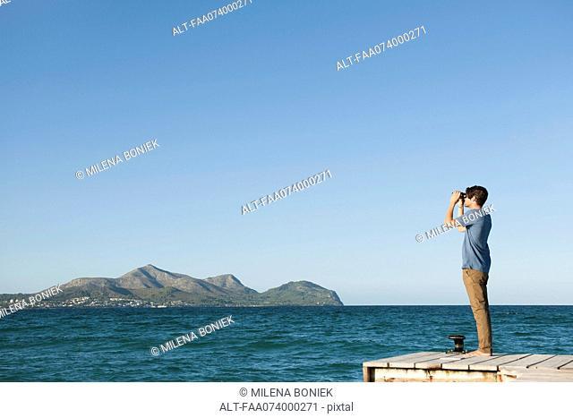 Man standing on pier looking at ocean view through binoculars, side view