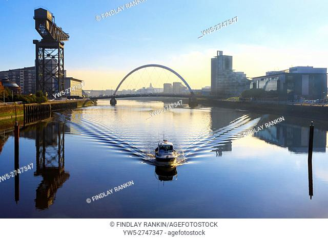 Early morning sunrise and mist over the River Clyde with the Anderston Crane and Arc (Squinty) Bridge, Glasgow< Scotland, UK
