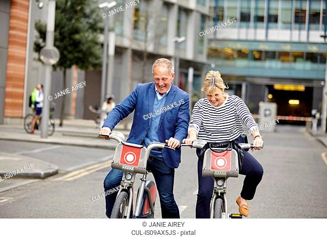 Mature dating couple laughing whilst cycling on hire bicycles, London, UK