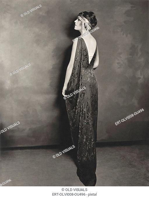 Full length profile of young woman in evening gown
