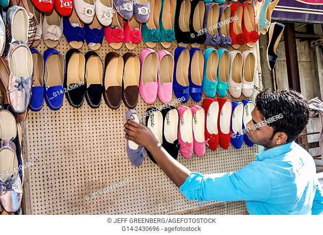 India, Asian, Mumbai, Apollo Bandar, Colaba, Indumati Sakharkar Marg, Causeway, Market, shopping, man, sidewalk vendor, woman's, shoes, setting up shop, sale