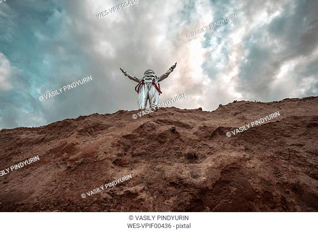 Spaceman standing on slope of nameless planet