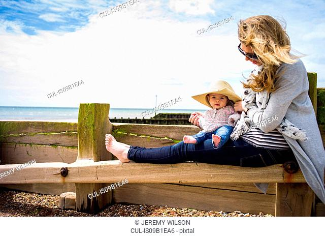 Baby girl wearing sun hat sitting on groyne with mother