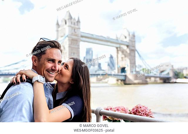 UK, London, happy couple kissing with the Tower Bridge in the background