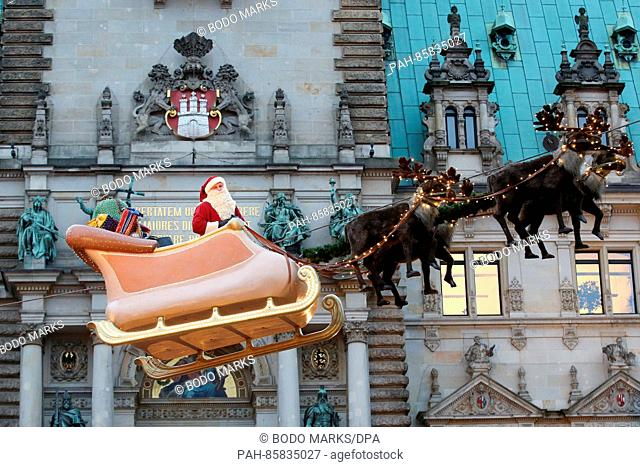 A Santa Claus impersonator stands on a hovering sleigh at the Historical Christmas Market outside of city hall in Hamburg,Germany, 21 November 2016