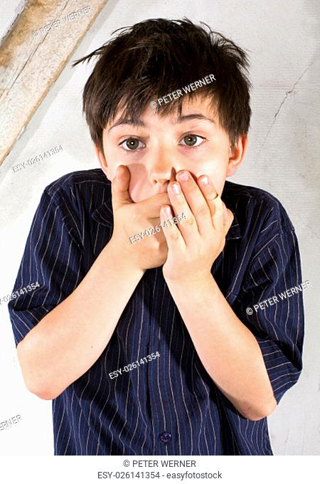 portrait of a young boy in a shirt with his hands on his mouth looking scraed and surprised