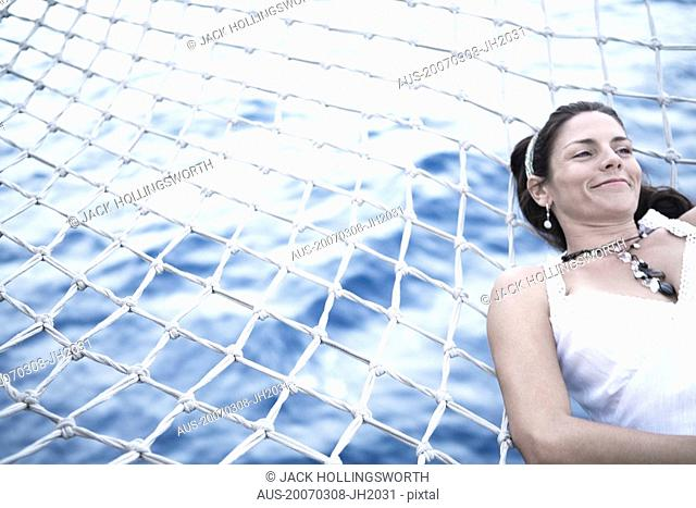 Mid adult woman lying on the net of a ship and smiling
