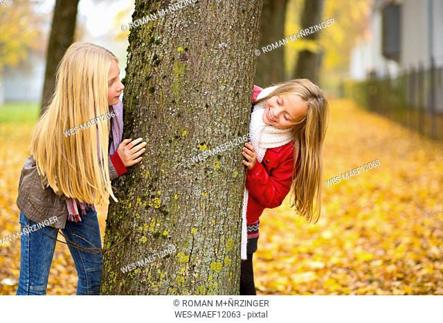 Two girls playing hide and seek in autumn