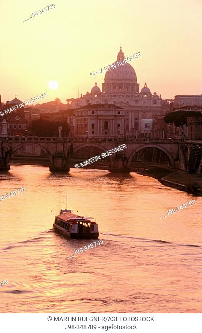 View on St. Angelo bridge over Tiber river and St. Peter's basilica in background. Vatican City, Rome. Italy