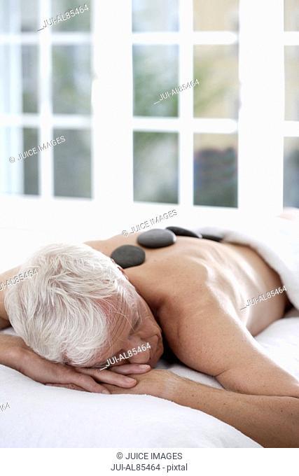 Senior man getting spa stone treatment