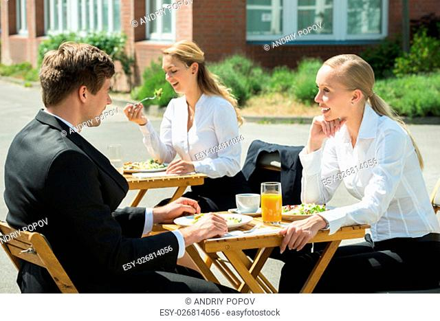Young Happy Male And Female Businesspeople Eating Food In Restaurant