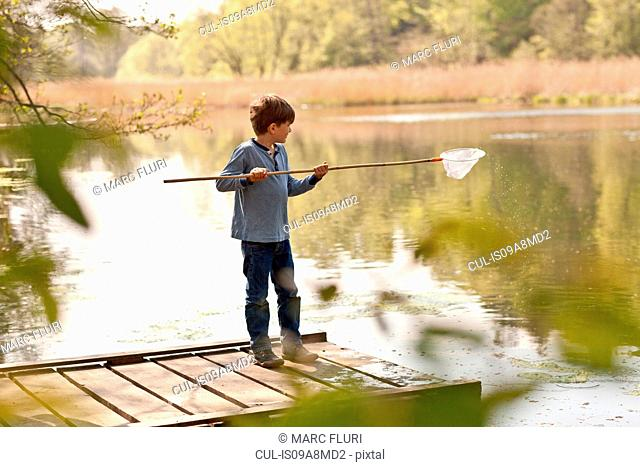 Boy standing on pier and fishing in river