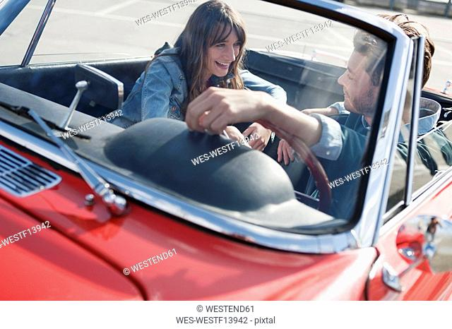 Germany, Berlin, Young couple sitting in cabriolet, laughing