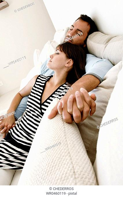 Young couple sleeping on a couch