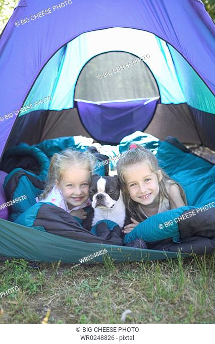 Sisters and dog in a tent