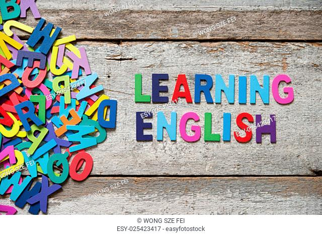"""The colorful words """"""""LEANRING ENGLISH"""""""" made with wooden letters next to a pile of other letters over old wooden board"""