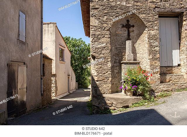 Crucifix shrine in wall alcove on village sidewalk