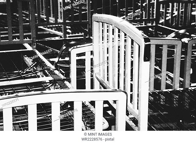 Empty hospital bed frames, stacked up in a pile in an empty room