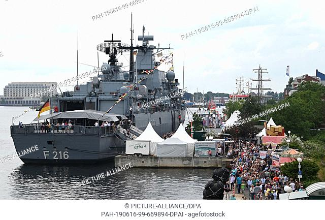 """16 June 2019, Lower Saxony, Wilhelmshaven: The frigate """"""""Schleswig-Holstein"""""""" is located at the Ems-Jade canal while visitors walk along it during the festival..."""