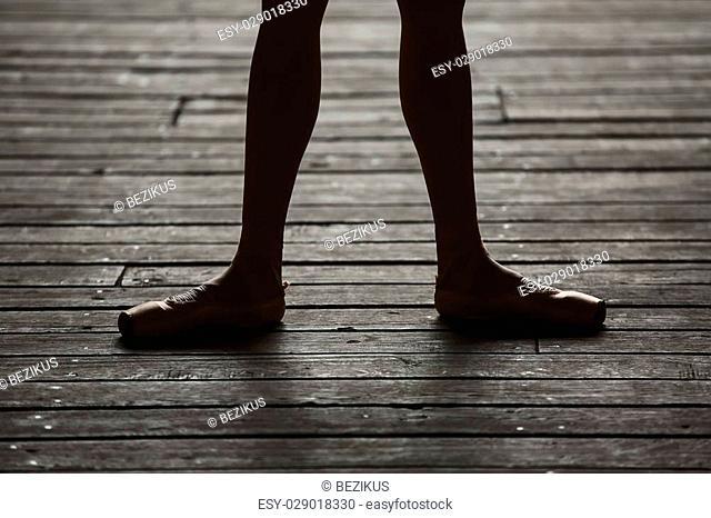 Photo of graceful ballerina dancing feet on the floor in backlit