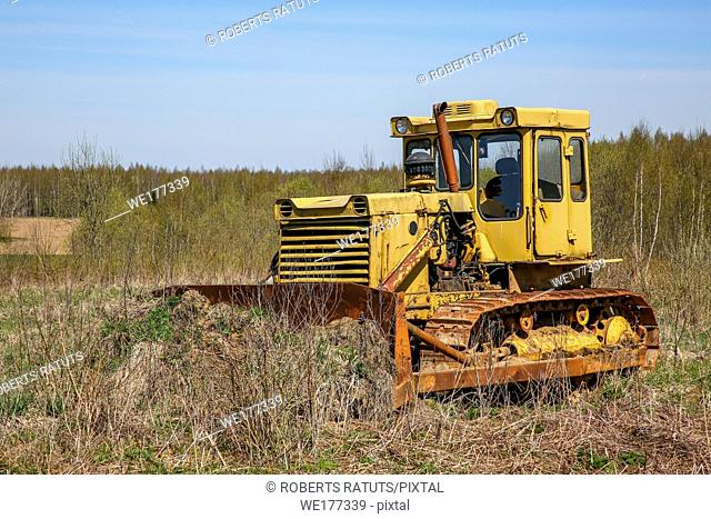 Old yellow rusty crawler tractor in the field. Old crawler tractor on overgrown field, Latvia