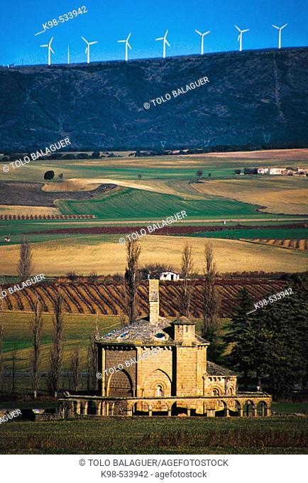 Santa Maria de Eunate (Romanico s.XII) y parque eolico del perdon al fondo. Muruzabal. Navarra. Spain