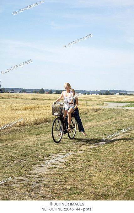 Two girls riding bike through field