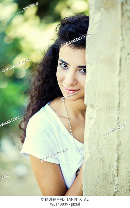 Happy Middle Eastern girl leaning on the wall outdoors
