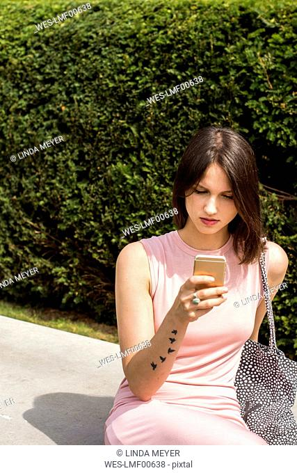 Young woman sitting on bench using smartphone