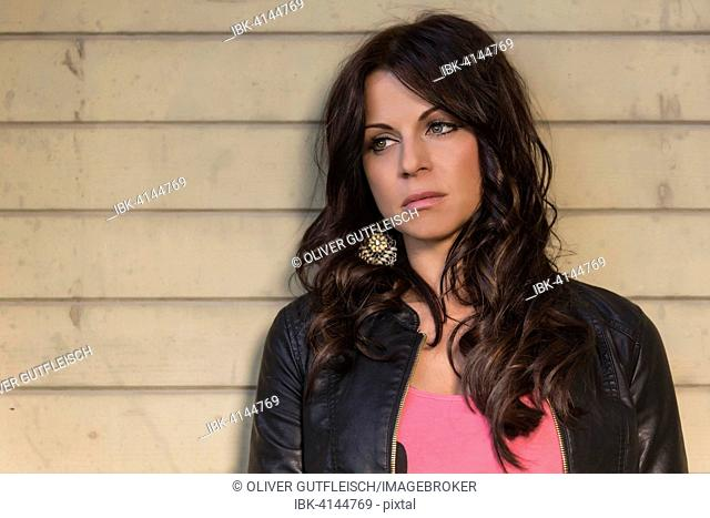 Young woman, frustrated, in black leather jacket, looks thoughtful, portrait