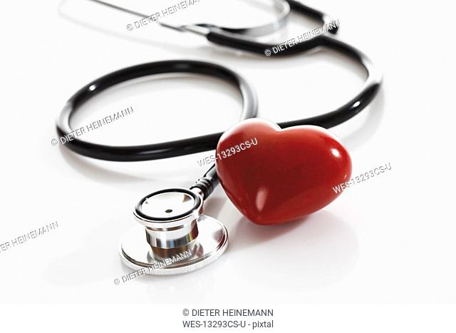 Stethoscope with heart shape object on white background, close up
