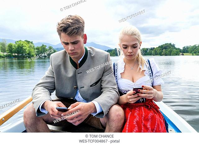 Germany, Bavaria, portrait of young couple sitting in a rowing boat on Staffelsee looking at their cellphones