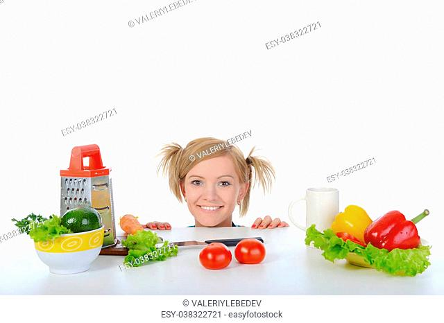 smiling blonde looks for fresh vegetables. Isolated on white background