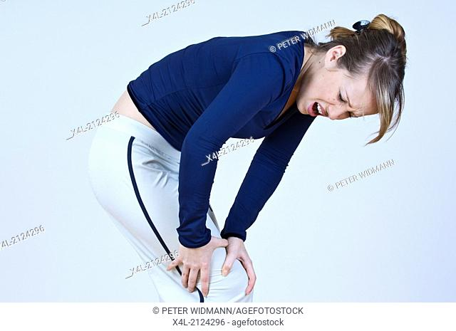 young woman bending over, having pain (model-released)