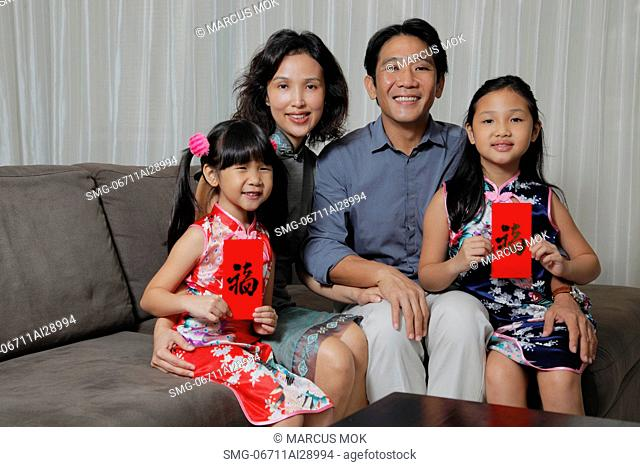 Chinese family sitting together with daughters holding red envelopes Hong Bao