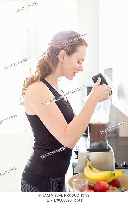 Mid-adult woman preparing smoothie